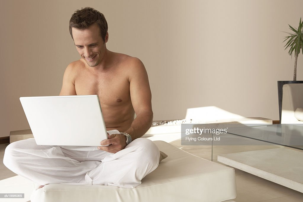 Half-dressed Man Sitting Cross Legged in a Living Room Using a Laptop Computer : Stock Photo