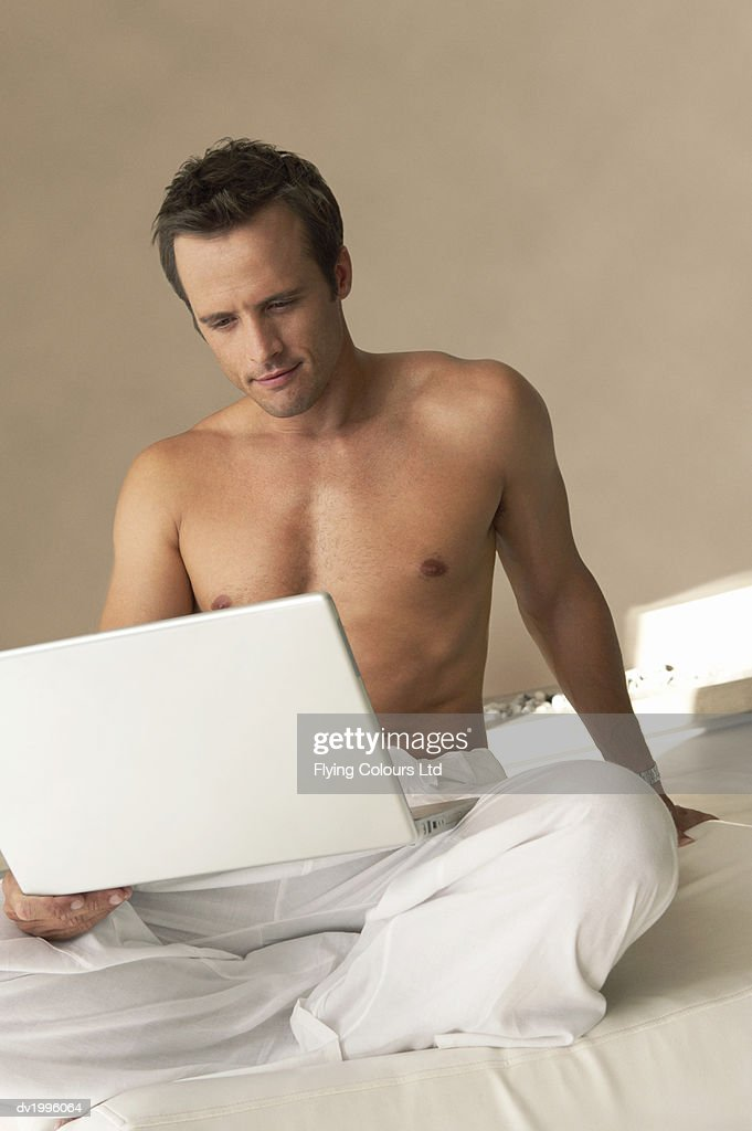 Half-dressed Man Sitting Cross Legged on a Bed Using a Laptop Computer : Stock Photo