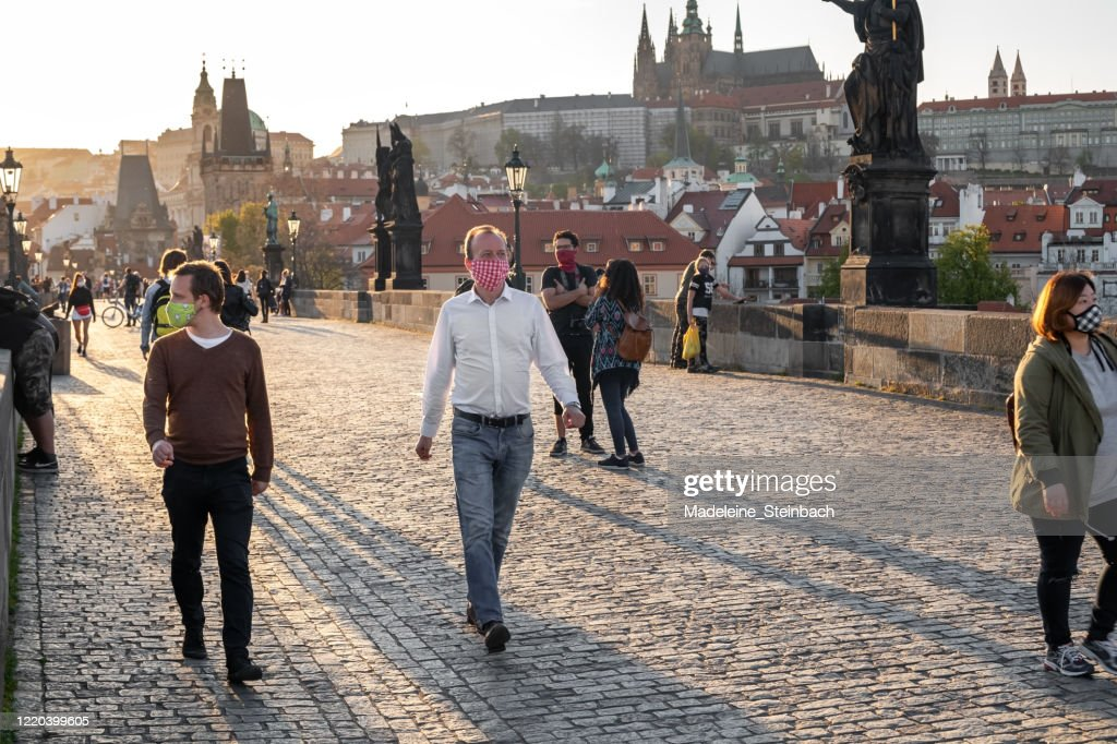 Half-empty Charles Bridge in Prague during the coronavirus pandemic, with people wearing face masks : Stock Photo