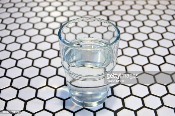 half-full water glass on a tiled table - half full stock photos and pictures