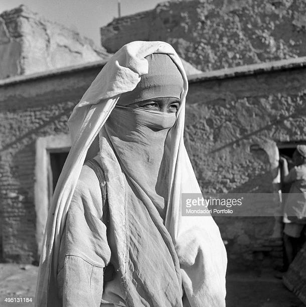 Halflength portrait of a Moroccan woman wearing the traditional clothes called djellabah and the veil that covers her face in these years some...