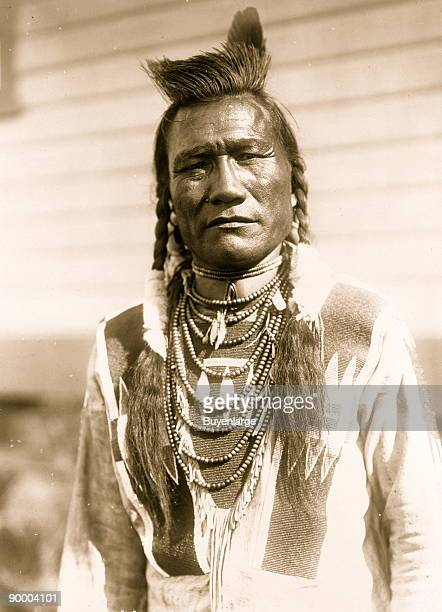 Halflength portrait of American Indian man facing front wearing beaded buckskin shirt one feather and loop necklace