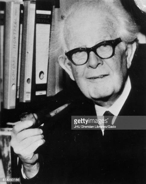 Halflength portrait of clinical psychologist Jean Piaget wearing a dark suit and dark glasses standing in front of a bookshelf smoking a pipe with a...