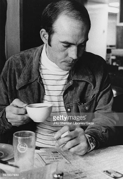 A halflength portrait of founder of the gonzo journalism movement Hunter Thompson as he intently reads the newspaper while drinking a cup of coffee...