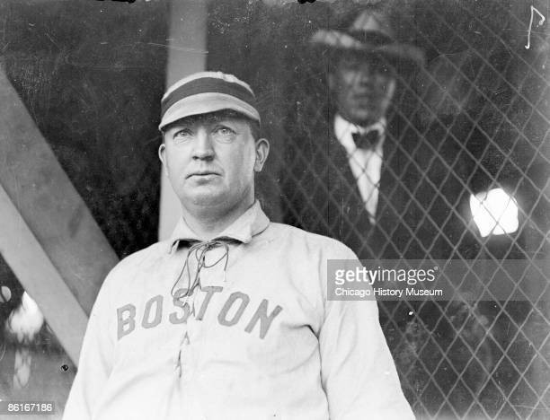 Halflength portrait of Hall of Famer Cy Young pitcher for the Boston American League team standing by grandstand concourse netting at South Side Park...