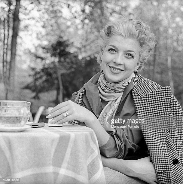Halflength portrait of smiling Isa Barzizza sitting at a small tea table in a garden an overcoat on her shoulders the multifaceted actress ironic and...