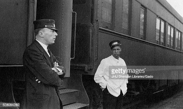 Halflength portrait of two conductors standing outside of a train one a white man with his arms crossed and wearing a suit the other an African...