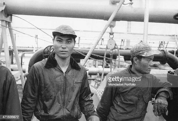 Halflength portrait of two workers wearing overalls and caps in a pause during work in the oil field behind them can be seen fuel extraction ducts...