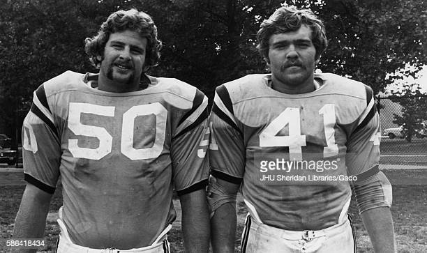 Halflength standing portrait of two Johns Hopkins University football players standing on a field 1970