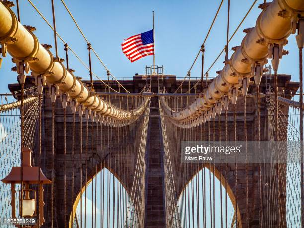 half-mast flag on brooklyn bridge, lower manhattan, new york city, usa - manhattan new york city stock pictures, royalty-free photos & images