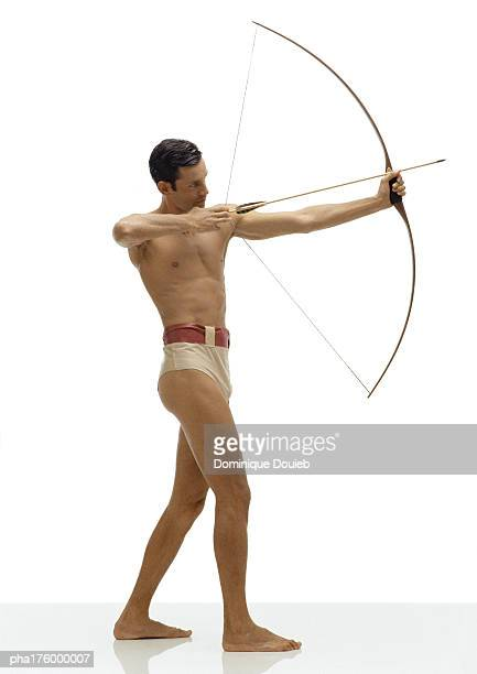 Half-nude man bending bow, side view