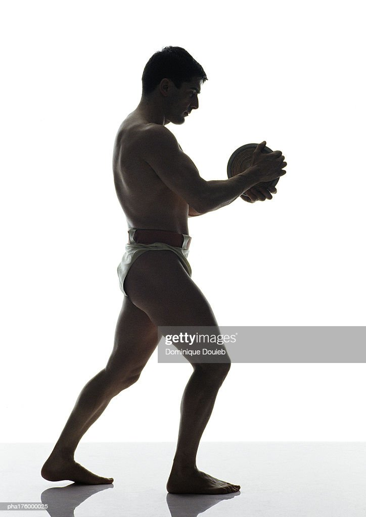 Half-nude man holding discus, side view : Stockfoto