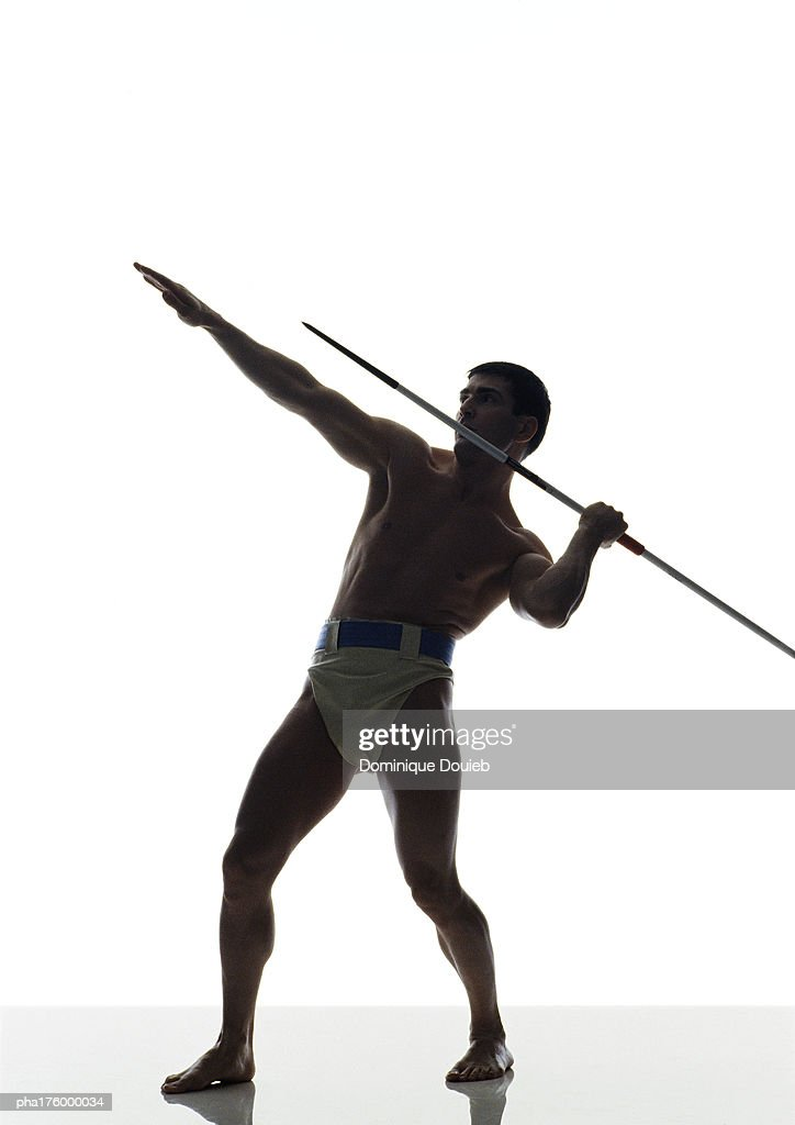 Half-nude man preparing to throw javelin, side view : Stockfoto