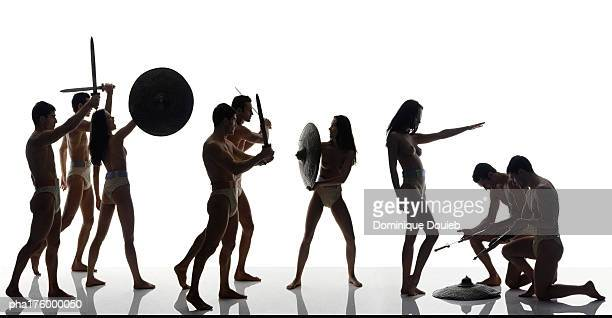 half-nude men and women with swords and shields - warrior person stock photos and pictures