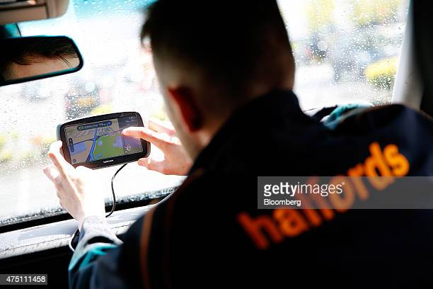A Halfords employee adjusts a TomTom navigation system manufactured by TomTom NV as it sits on a vehicle windscreen in Manchester UK on Friday May 29...