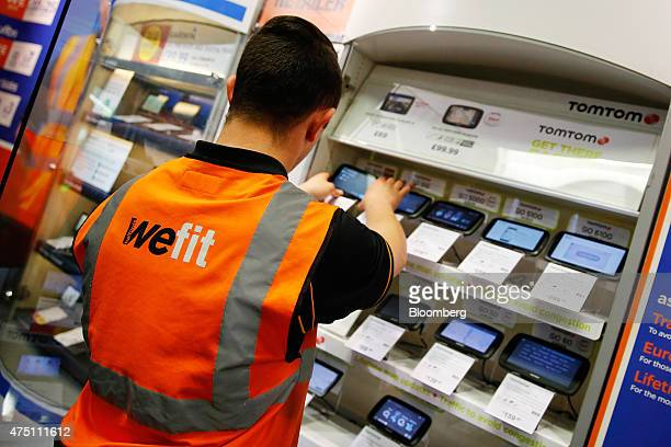 A Halfords employee arranges navigation systems manufactured by TomTom NV inside the Halfords Group Plc store in Manchester UK on Friday May 29 2015...