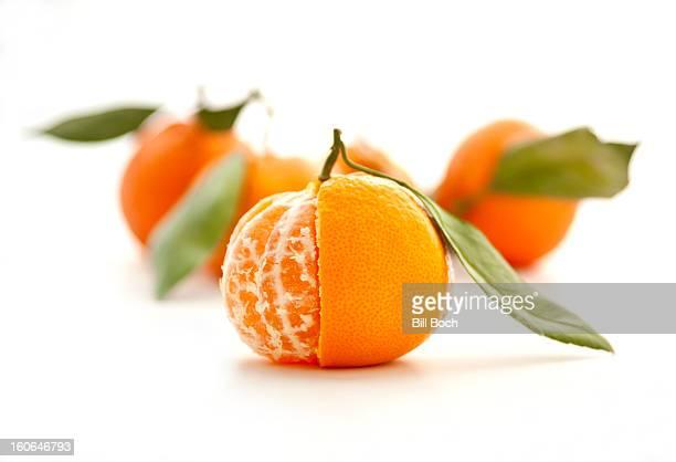 Half-peeled satsuma tangerine on white