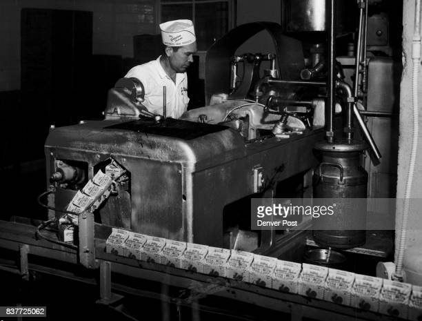 Halfpint containers of milk roll off the assembly line at the Garden Farm Dairy E 60th Ave and Albion St as John Peters of Derby operator watches the...