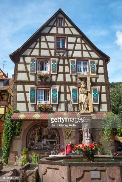 Half-timbered house with fountain in front of Sainte-Croix church