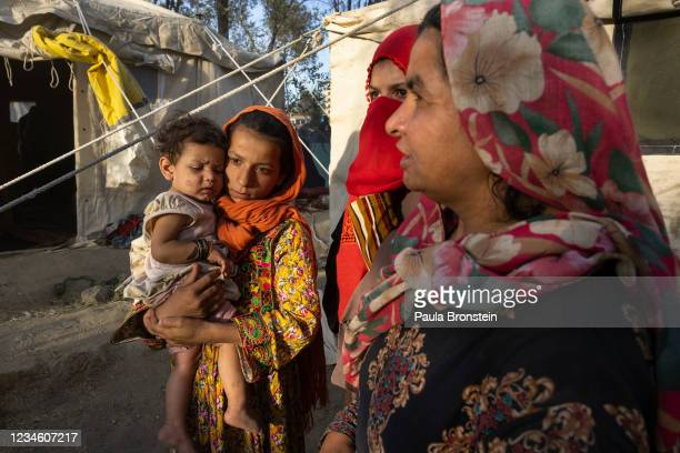 Halida from Tahar, who lost her father, killed by the Taliban holds her cousin Shafika, 8 months, along side family as displaced Afghans arrive at a...