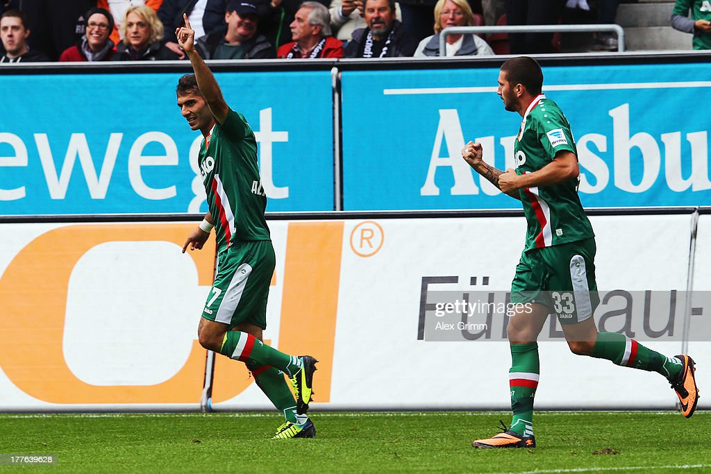 Halil Altintop (L) of Augsburg celebrates his team's first goal with team mate Sascha Moelders during the Bundesliga match between FC Augsburg and VfB Stuttgart at SGL Arena on August 25, 2013 in Augsburg, Germany.
