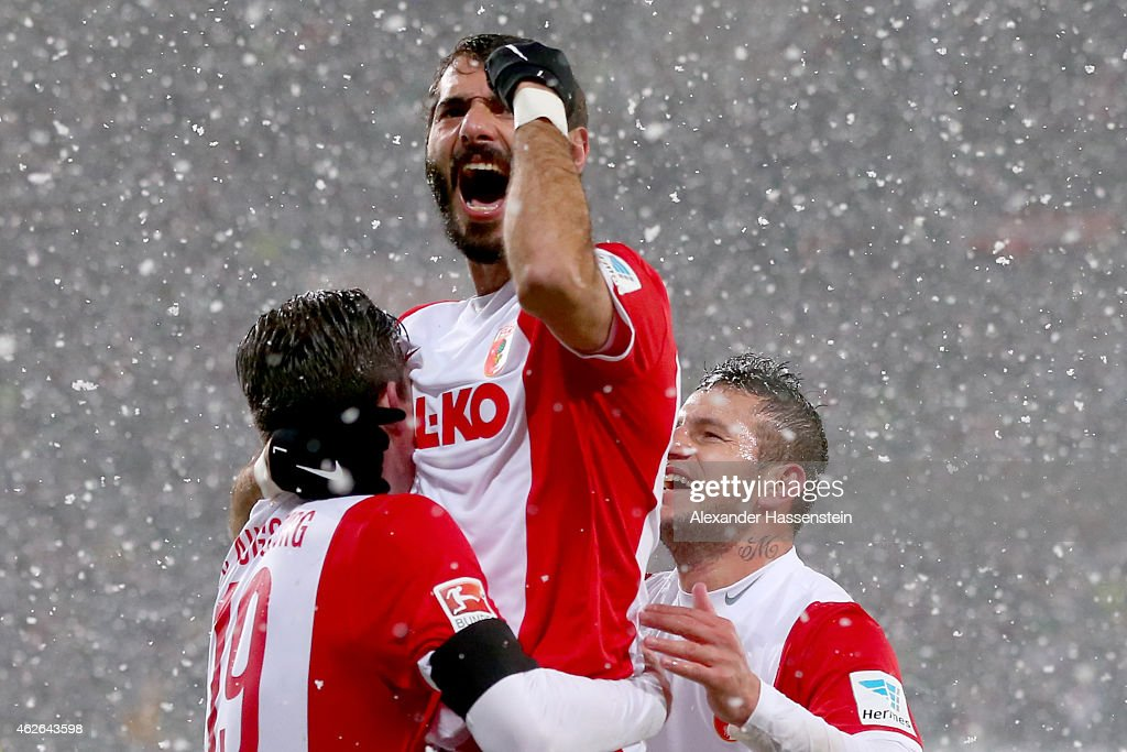 Halil Altintop (C) of Augsburg celebrates his team's first goal with team mates Pierre-Emile Hojbjerg (L) and Raul Bobadilla during the Bundesliga match between FC Augsburg and 1899 Hoffenheim at SGL Arena on February 1, 2015 in Augsburg, Germany.