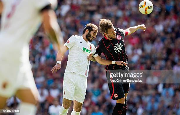 Halil Altintop of Augsburg jumps for a header with Marco Russ of Frankfurt during the Bundesliga match between Eintracht Frankfurt and FC Augsburg at...