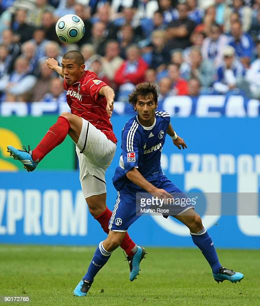 Halil Altintop of Schalke and Du RI Cha of Freiburg jump for a header during the Bundesliga match between FC Schalke 04 and SC Freiburg at the...