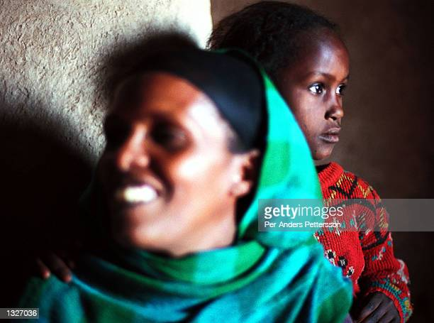 Halima Becker and her daughter Misra stand by a window in their home February 9 2001 in the Erer Valley in eastern Ethiopia Halima is an activist...