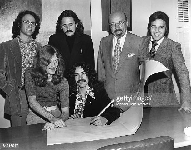 Hall and Oates sign their Atlantic Records contract in 1972 in New York City New York Atlantic founder Ahmet Ertegun is behind them second from the...