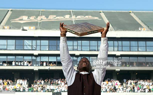Hall of Fame baseball player Rickey Henderson holds up a golden base during a ceremony to retire his number 24 by the Oakland Athletics before the...