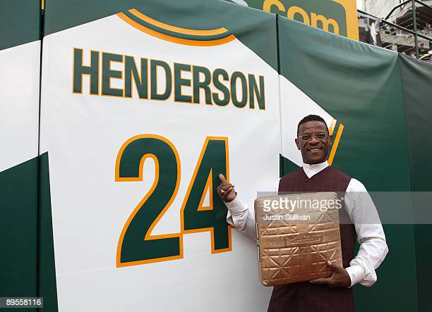 Hall of Fame baseball player Rickey Henderson stands in front of his retired jersey during a ceremony to retire his number 24 by the Oakland...