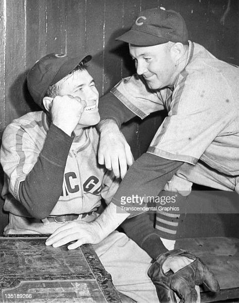 Hall of Fame baseball players Dizzy Dean left and Gabby Hartnett josh around in the clubhouse at Braves Field in Boston Massachusetts circa 1938