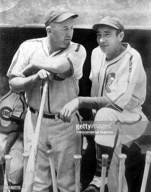 Hall of Fame baseball players Gabby Hartnett left and Tony Lazzari talk it over on the dugout steps during a game in Wrigley Field in Chicago...