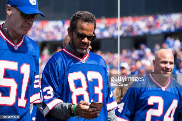 Hall of Fame former Buffalo Bills player Andre Reed looks at a phone before participating in a halftime celebration during the game between the...