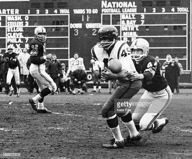 Hall of Fame halfback Bobby Mitchell of the Washington Redskins makes a catch while Steelers defensive back Bill Daniels attempts to bring him down...