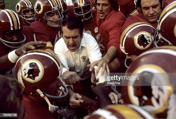Hall of Fame head coach George Allen of the Washington Redskins in a pregame huddle with his players in a November 1975 home game at RFK Stadium in...