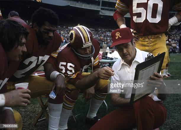 Hall of Fame head coach George Allen of the Washington Redskins on the sidelines discussing defensive strategy with linebacker Chris Hamburger and...