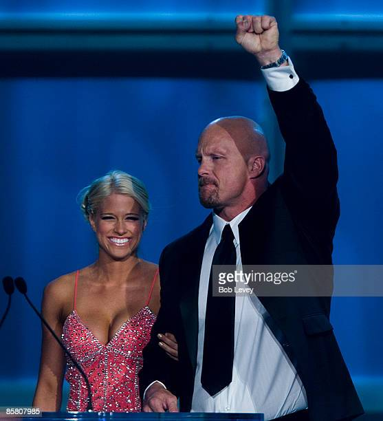 Hall of Fame inductee Stone Cold Steve Austin is escorted to the stage by WWE Diva Kelly Kelly as he attends the 25th Anniversary of WrestleMania's...