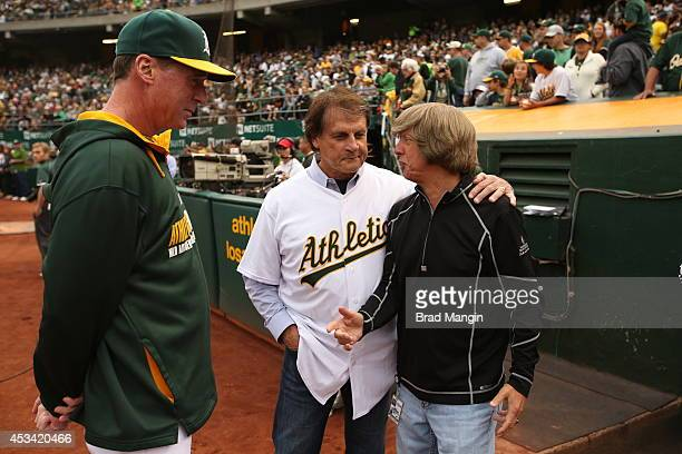 Hall of Fame Manager Tony La Russa talks with manager Bob Melvin and director of team travel Mickey Morabito of the Oakland Athletics before the game...
