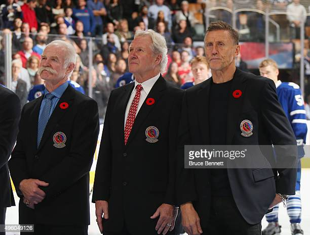 Hall of Fame members Lanny McDonald Darryl Sittler and Borje Salming stand at attention during the national anthem prior to the game between the...