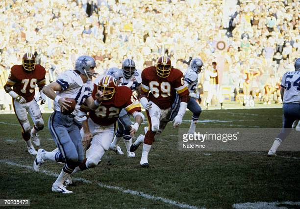 Hall of Fame quarterback Roger Staubach of the Dallas Cowboys rolls out and tries to elude Redskins defensive end Dallas Hickman during the Cowboys...