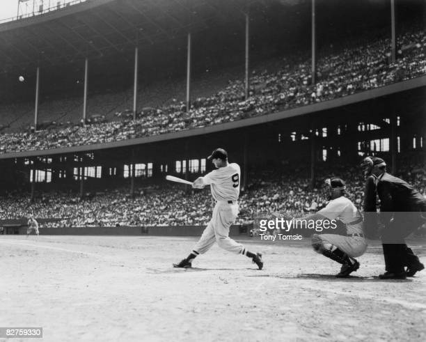 Hall of Fame slugger Ted Williams of the Boston Red Soxs hits one of his 521 career home runs during a game against the Cleveland Indians at...