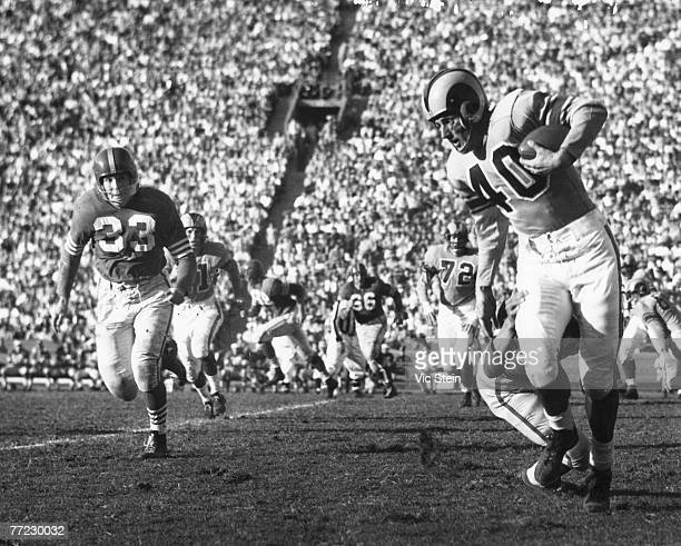 Hall of Fame wide receiver Elroy 'Crazylegs' Hirsch of the Los Angeles Rams avoids a tackler as Hardy Brown of the San Francisco 49ers give chase in...