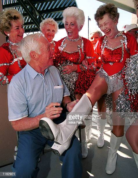 Hall of Fame Yankees pitcher Whitey Ford autographs the boot of 81yearold Sun City Poms member Pat Cross right prior to the grand opening of the Del...