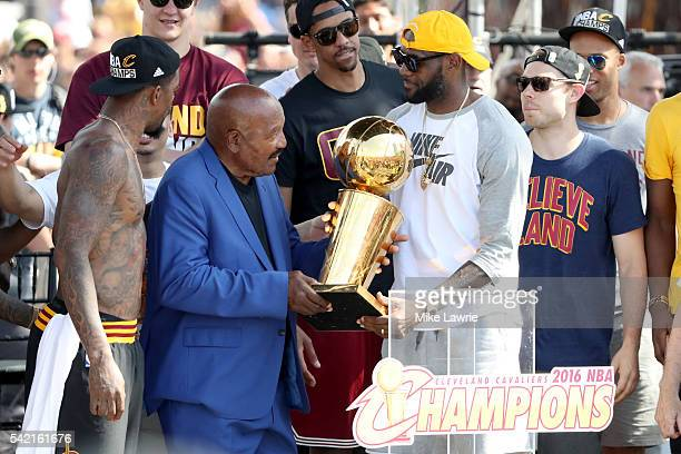 Hall of Famer and former Cleveland Brown Jim Brown hands the Larry O'Brien Trophy to LeBron James of the Cleveland Cavaliers during the Cleveland...