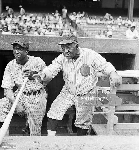 """Hall of Famer James """"Cool Papa"""" Bell and manager Jim Taylor stand on the dugout steps during a Chicago American Giants game. The Giants were a..."""