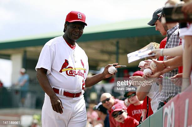 Hall of Famer Lou Brock of the St Louis Cardinals signs autographs prior to his team playing against the Atlanta Braves at Roger Dean Stadium on...