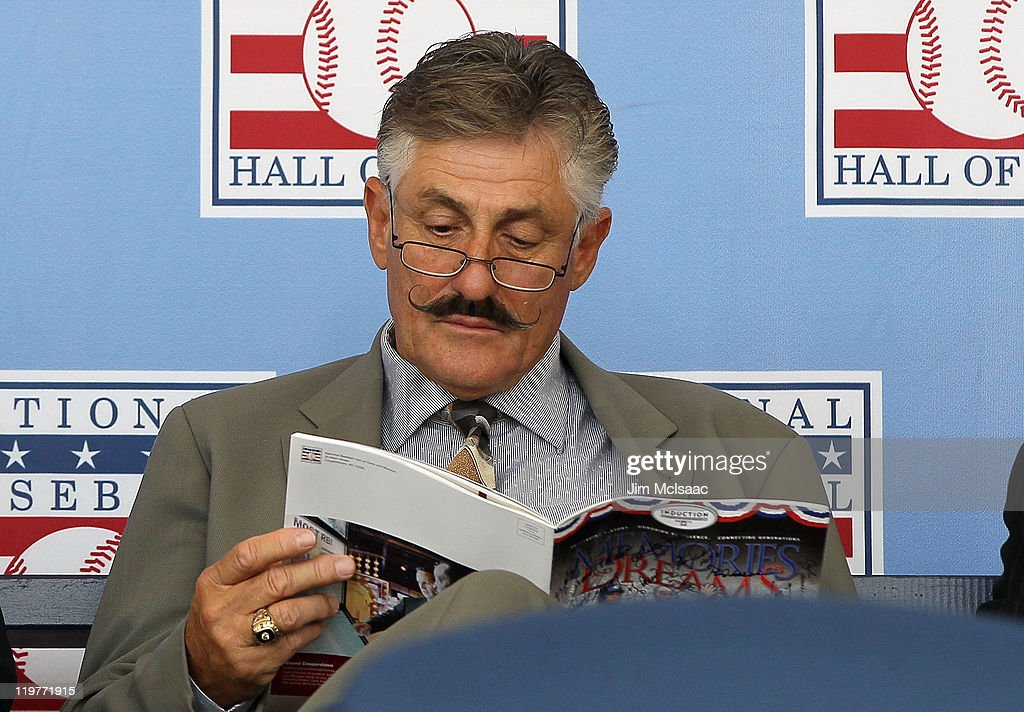 Hall of Famer Rollie Fingers reads the official program at Clark Sports Center during the Baseball Hall of Fame induction ceremony on July 24, 2011 in Cooperstown, New York.
