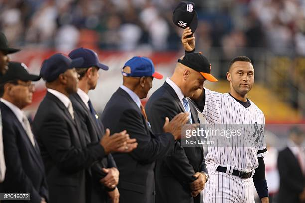 Hall of Famers Luis Aparicio Ozzie Smith Robin Yount Ernie Banks and Cal Ripken Jr look on as American League AllStar Derek Jeter of the New York...